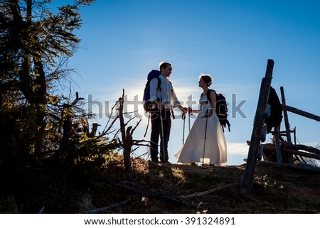 Beautiful tourist wedding couple standing against the sun. Alpine mountains background