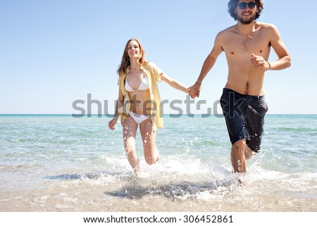 Beautiful tourist young couple holding hands and running together on the shore of a sandy beach with mountains and blue sea water and sky, outdoors. Travel and tourism lifestyle, coastal destination.
