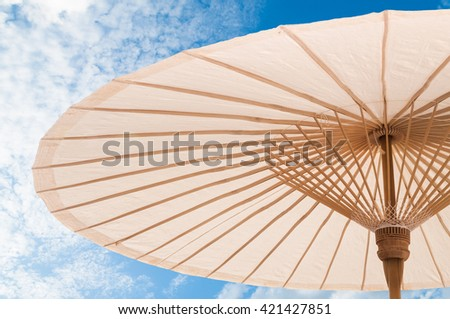 beautiful  Traditional Asian paper and bamoo umbrella with a rounded handle on blue sky - stock photo