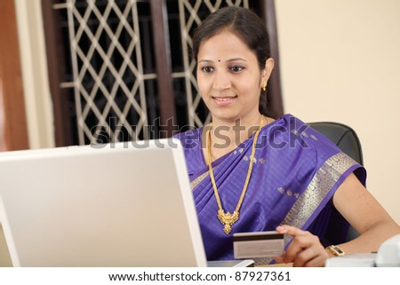Beautiful traditional woman sitting at home and shopping with laptop