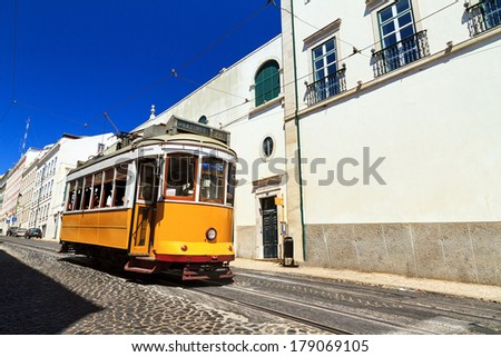 Beautiful traditional yellow tram in the streets of Lisbon, Portugal, in summer - stock photo