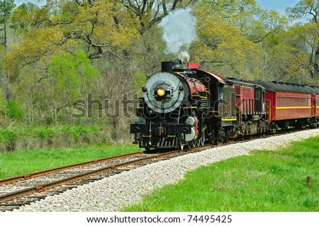 Beautiful train engine and cars on the track on a spring morning. - stock photo