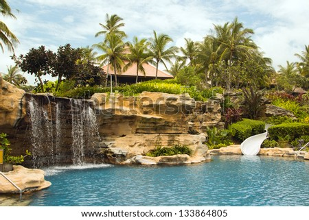 Beautiful tranquil deserted tropical resort rock pool with a waterfall feature and water slide surrounded by palm trees for an idyllic summer vacation - stock photo