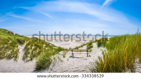 Beautiful tranquil dune landscape with idyllic bench overlooking the German North Sea and a long beach on the island of Amrum, Schleswig-Holstein, Germany - stock photo