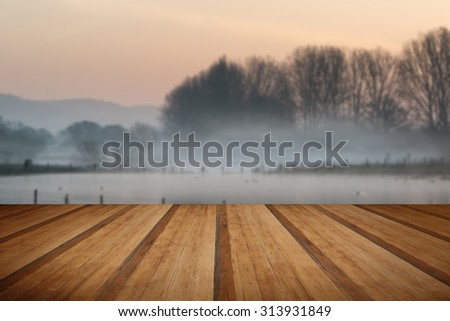 Beautiful tranquil landscape of lake in mist with wooden planks floor - stock photo