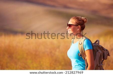 Beautiful traveler girl enjoying golden wheat field in sunset light, beautiful summer nature, farmland in Europe, travel and tourism concept - stock photo
