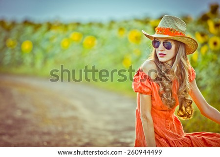 Beautiful traveler in rural scenery over  rural road  and sunflower field. toned vintage image, soft light - stock photo