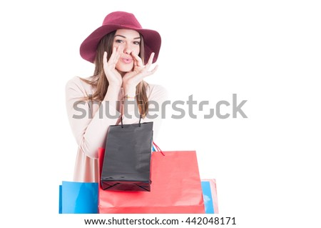 Beautiful trendy girl at shopping carrying colorful gift bags whistle for somebody isolated on white background with copy space area - stock photo