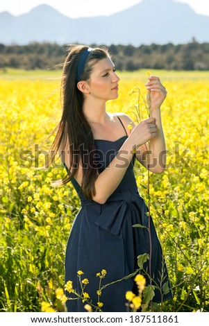 Beautiful trendy young woman in a field of yellow rapeseed holding up a spray of flowers as she examines them while enjoying a summer day in the countryside - stock photo