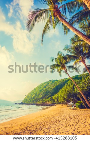 Beautiful tropical beach and sea landscape with coconut palm tree and umbrella and chair - Vintage Filter and Boost up color Processing