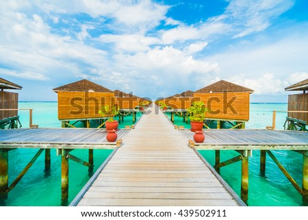 Beautiful tropical beach and sea with water bungalow on blue sky in Maldives island - Boost up color Processing - stock photo