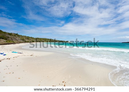 Beautiful tropical beach at Half Moon Bay Antigua island in Caribbean with white sand, turquoise ocean water and blue sky - stock photo