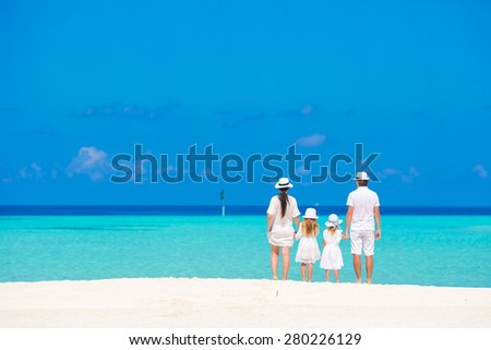 Beautiful tropical beach landscape with family in white enjoying summer vacation - stock photo