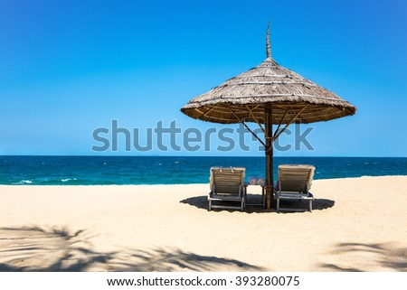 Beautiful tropical beach: straw umbrella, beach beds and palm trees shade - stock photo