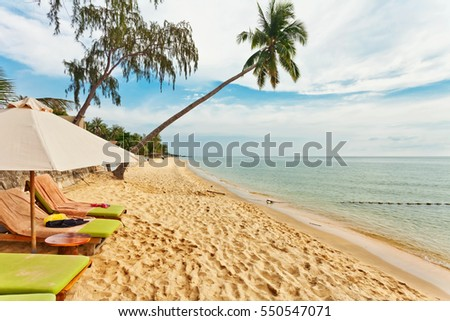 Beautiful tropical beach with  lounges and palms under blue sky at Phu Quoc island  in Vietnam.