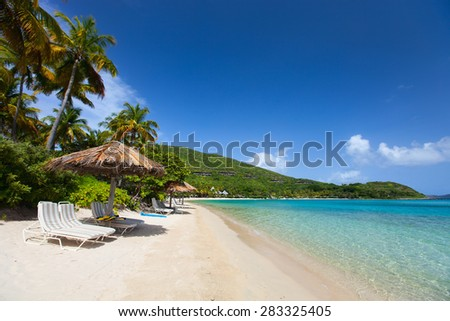 Beautiful tropical beach with palm trees, white sand, turquoise ocean water and blue sky at British Virgin Islands in Caribbean - stock photo