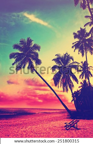 Beautiful tropical beach with silhouettes of palm trees at sunset. Travel background with retro vintage instagram filter.  - stock photo