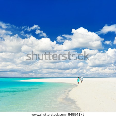 beautiful tropical landscape. senior couple walking on a beach - stock photo