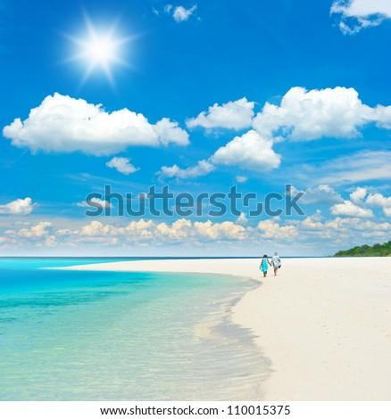 beautiful tropical landscape. senior couple walking on the beach - stock photo