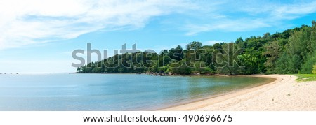 Beautiful tropical sandy beach and calm sea landscape with trees and blue sky background panorama. Layan beach on Phuket island, Thailand.