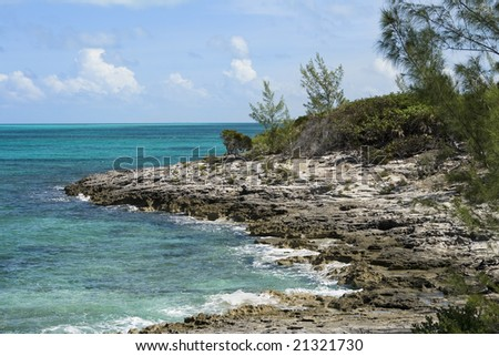 Beautiful tropical shoreline with green clear water crashing into volcanic rock. - stock photo