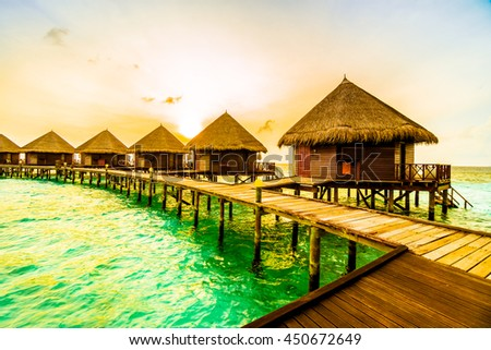 Beautiful tropical Sunset over maldives island with water bungalow in hotel resort - Vintage Filter and Boost up color Processing