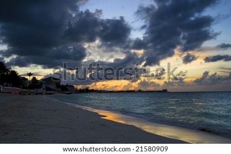 Beautiful tropical sunset with a nice reflection off the water's edge. - stock photo