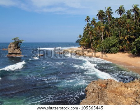 Beautiful tropical wild beach with an rocky islet and lush vegetation - stock photo