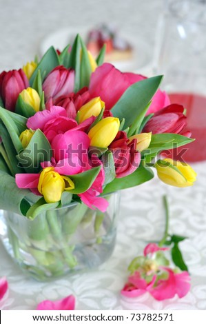 Beautiful tulips and peonys in a glass vase - stock photo