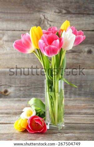 Beautiful tulips in vase on grey wooden background - stock photo