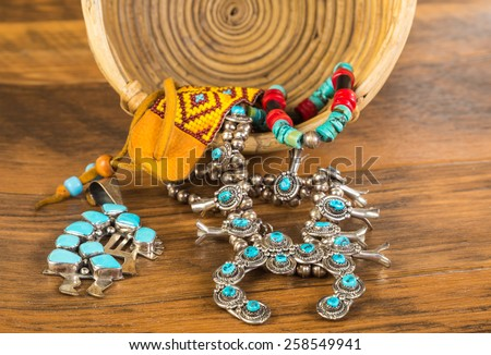 Beautiful turquoise and silver symbolic Native American jewelry spilling from vintage wicker basket onto rustic wooden floor. - stock photo