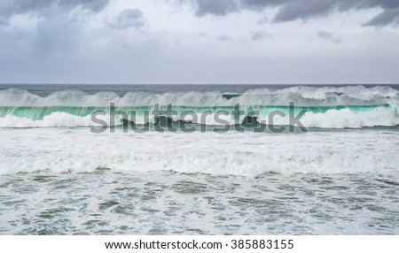 Beautiful turquoise ocean waves rolling over, with foamy water and dramatic dark cloudy sky. Suitable for background texture. - stock photo
