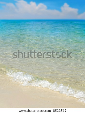Beautiful turquoise sea and gentle waves with cloudscape in distance - stock photo