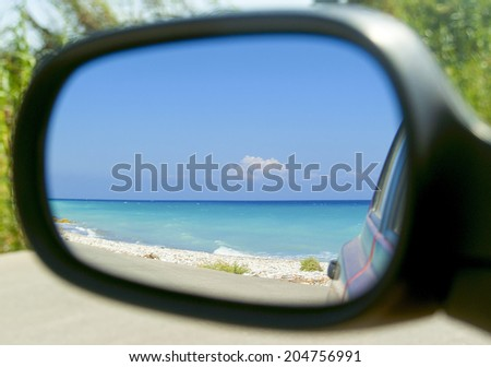 Beautiful turquoise sea view in side mirror of car - stock photo