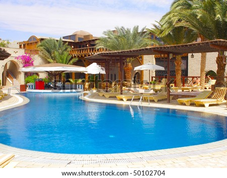 Beautiful turquoise swimming pool with sun loungers and palm trees