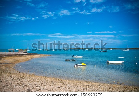beautiful turquoise waters of the islands of the bahamas with many sailing and fishing boats anchored in the harbor of Black Point Sound in Exuma - stock photo