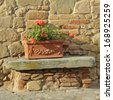 beautiful tuscan terracotta planter in front of  old stone and brick house, Italy, Europe - stock photo