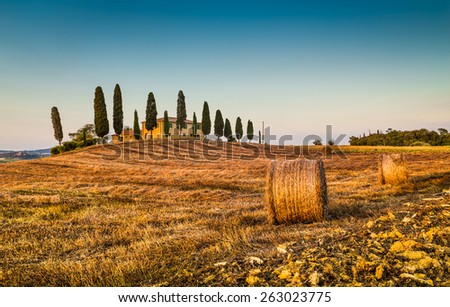 Beautiful Tuscany landscape with traditional farm house and hay bales in golden evening light, Val d'Orcia, Italy - stock photo