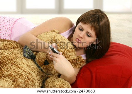 Beautiful twenty something woman in pajamas with pillow and remote control. - stock photo
