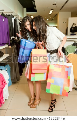 Beautiful twin females in shopping boutique, one looking in the shopping bag of the other - stock photo