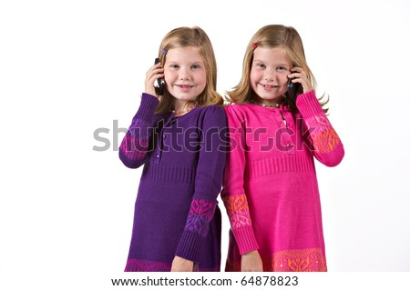 Beautiful twin girls on cell phones - stock photo