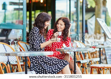 Beautiful twin sisters drinking coffee in a cozy outdoor cafe in Paris, France. Happy smiling girls enjoy their vacation in Europe - stock photo