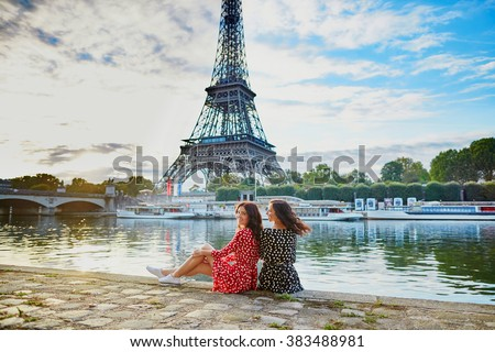 Beautiful twin sisters in red and black polka dot dresses in front of the Eiffel tower near the river Seine in Paris, France - stock photo