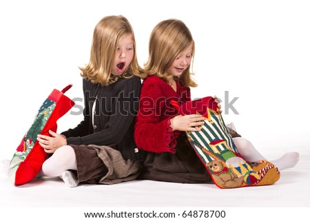 Beautiful twin sisters opening Christmas gifts - stock photo