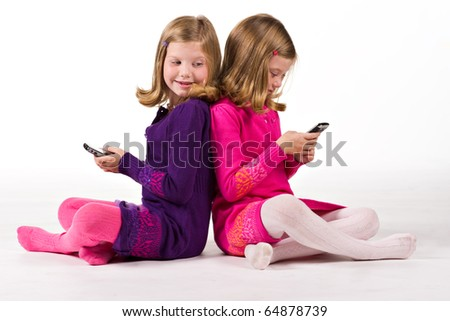 Beautiful twin sisters send text messages - stock photo