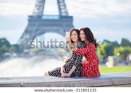Beautiful twin sisters taking selfie in front of Eiffel Tower while traveling in Paris, France. Happy smiling girls enjoy their vacation in Europe - stock photo