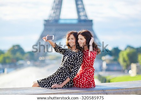 Beautiful twin sisters taking selfie in front of Eiffel Tower while traveling in Paris, France. Happy smiling girls enjoy their vacation in Europe