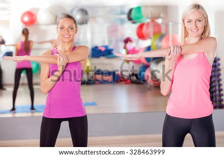 Beautiful two slim girls are warming their body in gym. They are standing and stretching arms sideways. The young women are looking at camera and smiling - stock photo