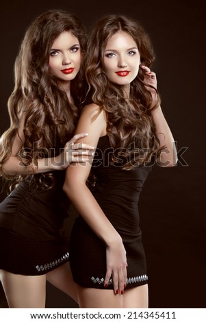 Beautiful two Young women with long healthy wavy hair styling and red lips posing in dress isolated on black background - stock photo