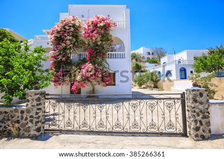 Beautiful typical greek house with bougainvillea flowers Thira, Santorini island, Greece - stock photo